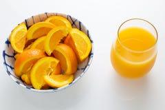 Vers gedrukt jus d'orange in een glas naast een kom van oranje plakken en twee die sinaasappelen enkel van de boom op een witte l stock afbeeldingen