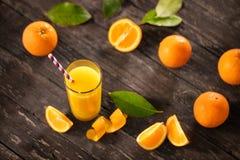 Vers gedrukt jus d'orange met halve sinaasappelen op houten lijst stock foto