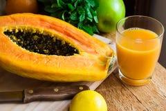 Vers gedrukt papajasap in glas, rijp gehalveerd fruit op houten scherpe raad stock fotografie