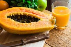 Vers gedrukt papajasap, rijp fruit op houten lijst, pepermunt, appelen stock afbeelding