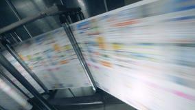Vers gedrukte krant op een typografietransportband stock videobeelden