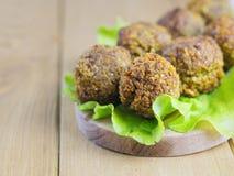 Vers gemaakt falafel op een saladeblad op een knipselraad op een bruine houten lijst Royalty-vrije Stock Fotografie