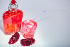 Vers gemaakt Granaatappelsap met volledige fles en glas met stro stock afbeelding