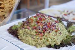 Vers gemaakt guacamole dompel op een witte die plaat onder op een een buffetbar of restaurant wordt voorbereid stock afbeelding