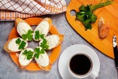 Vers gemaakte sandwiches met roomkaas en peterselie op een plaat, hakkende houten raad en een kop van koffie - ochtend en stock afbeelding