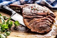 Vers geroosterd tomahawklapje vlees op leiplaat met zoute van de peperrozemarijn en peterselie kruiden Gesneden stukken van sappi royalty-vrije stock afbeeldingen
