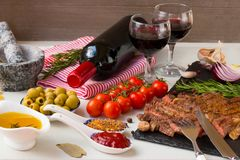 Vers geroosterd vlees Het geroosterde middelgrote braadstuk van het rundvleesentrecôte op zwarte steenraad, rode wijn en twee vol Royalty-vrije Stock Afbeelding