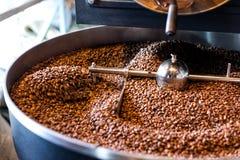 Vers geroosterde koffiebonen van een grote grill in de koelcilinder Motieonduidelijk beeld op bonen Stock Foto's