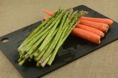 Vers gespoelde asperge en wortelen stock afbeelding