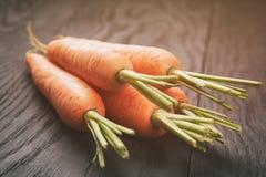 Vers gewassen gehele wortelen op oude houten lijst stock foto's