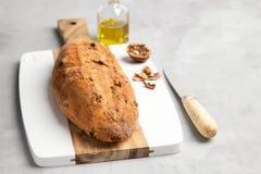 Vers gezond brood met okkernoten en rozijnen op scherpe raad op grijze steenachtergrond stock foto