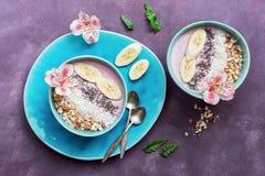 Vers gezond ontbijt - de yoghurt met banaan, amandel, kokosnoot schilfert af, chiazaden in een blauwe die kom met bloemen op purp stock fotografie