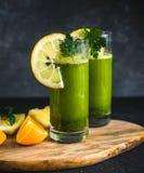 Vers groen die sap van peterselie, sinaasappelen en citroenen wordt gemaakt royalty-vrije stock afbeelding