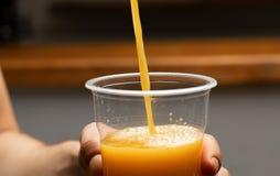 Vers het gedrukte jus d'orangestroom gieten in meeneem plastic beschikbaar die glas in een hand van een jonge mens, close-upsprui royalty-vrije stock afbeeldingen