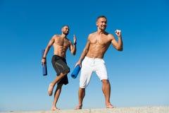Vers la santé Les hommes dépêchent la pratique en matière extérieure de yoga Hommes musculaires s'exerçant sur l'air frais Force  image stock