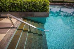 Vers le bas escalier avec la barre dans la piscine Photo stock