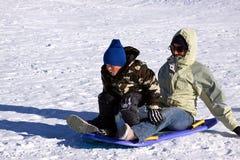 vers le bas fils sledding de mère de côte Photos libres de droits