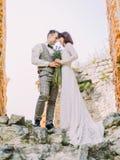 Vers le bas la vue des nouveaux mariés gais jugeant le bouquet et la position de mariage tête à tête Photos stock