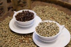 Vers le haut de du café avec des grains de café entièrement sur le plateau Photo stock