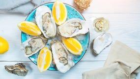 Vers oestersclose-up op blauwe plaat, gediende lijst met oesters, citroen en champagne in restaurant Gastronomisch voedsel stock fotografie