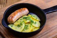 Vers ontbijt in een oude pan met gebraden die worsten en aardappels met groene dille worden bestrooid De traditionele dinerdienst stock foto