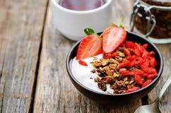 Vers ontbijt van granola, yoghurt, noten, gojibessen en stro Stock Afbeelding