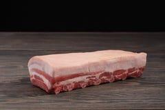 Vers ruw geheel rek van varkensvleeslendestuk met ribben en vet op een donkere achtergrond Stock Foto
