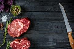 Vers ruw rundvlees met basilicum en een twijg van rozemarijn met mes met een houten handvat op zwarte houten achtergrond Hoogste  Stock Foto