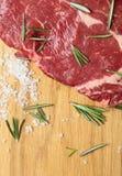 Vers ruw rundvleeslapje vlees op houten raad met rozemarijn en overzees zout stock foto