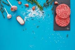 Vers ruw rundvleesvlees met kruiden en zout op turkooise achtergrond Stock Foto's