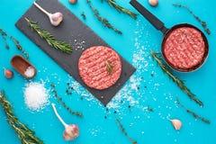 Vers ruw rundvleesvlees met kruiden en zout op turkooise achtergrond Stock Foto