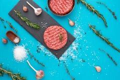 Vers ruw rundvleesvlees met kruiden en zout op turkooise achtergrond Royalty-vrije Stock Foto's