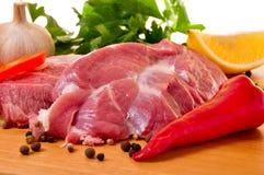 Vers ruw varkensvlees aan boord met verse groenten Royalty-vrije Stock Afbeeldingen