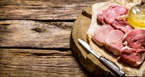 Vers ruw vlees met mes en olie op een houten tribune Royalty-vrije Stock Foto