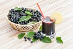 Vers sap van chokeberry of Aronia-melanocarpa in glas en bes in pot op houten stock afbeelding