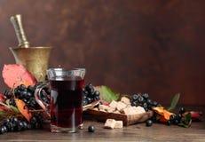 Vers sap van rijpe zwarte chokeberry in glas en bessen met l stock foto