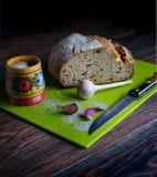 Vers tarwebrood, knoflook, een houten zoutvaatje met zout, een groene raad voor scherp brood, een mes Dit alles ligt op houten da royalty-vrije stock afbeeldingen