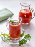 Vers tomatesap in een glasmok en in een pompoen met greens Stock Afbeeldingen