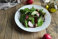 Vers voorbereide die salade van greens, rode radijzen en groene olijven wordt gemaakt stock foto
