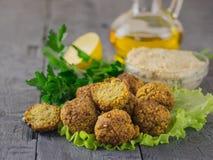 Vers voorbereidingen getroffen falafel met tahinideeg en olijfolie op de donkere houten lijst Stock Afbeeldingen