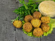 Vers voorbereidingen getroffen falafel met tahinideeg en olijfolie op de donkere houten rustieke lijst Stock Afbeelding