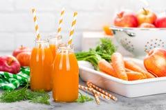 Vers wortel en appelsap op witte achtergrond Wortel en appelsap in glasflessen op witte lijst Apple en wortelsap Royalty-vrije Stock Afbeelding
