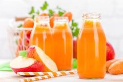 Vers wortel en appelsap op witte achtergrond Wortel en appelsap in glasflessen op witte lijst, close-up Stock Afbeeldingen