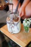 Versa il caffè in bicchiere di latte Immagine Stock