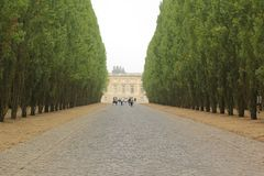 Versailles, France - August 27, 2017: Beautiful landscape with building and trees on the both sides stock photo