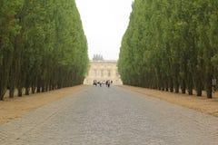 Versailles Frankrike - Augusti 27, 2017: Härligt landskap med byggnad och träd på de båda sidorna arkivfoto