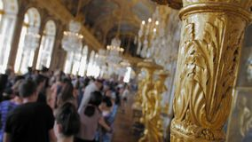 Versailles, PARIS, FRANCE- August 2018: Luxurious interior of the royal palace. Vintage candelabrum in the foreground. And a lot of tourists in the main hall stock video