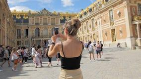 Versailles, PARIS, FRANCE- August 2018: unrecognized beautiful caucasian female tourist photographs the main entrance stock video footage
