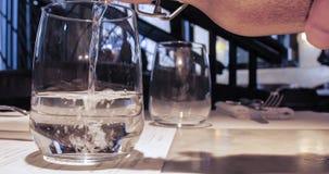Versamento del bicchiere d'acqua in un vetro da una bottiglia Fotografie Stock Libere da Diritti