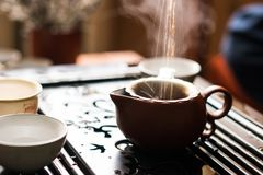Versamento del tè di Puer dalla teiera a cerimonia di tè del cinese tradizionale Insieme di attrezzatura per tè bevente Immagine Stock